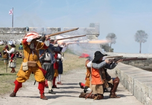 Searles Musketeers firing at the sea wall in St. Augustine. The direct result of the attack, the Castillo San Marcos , is in the background.